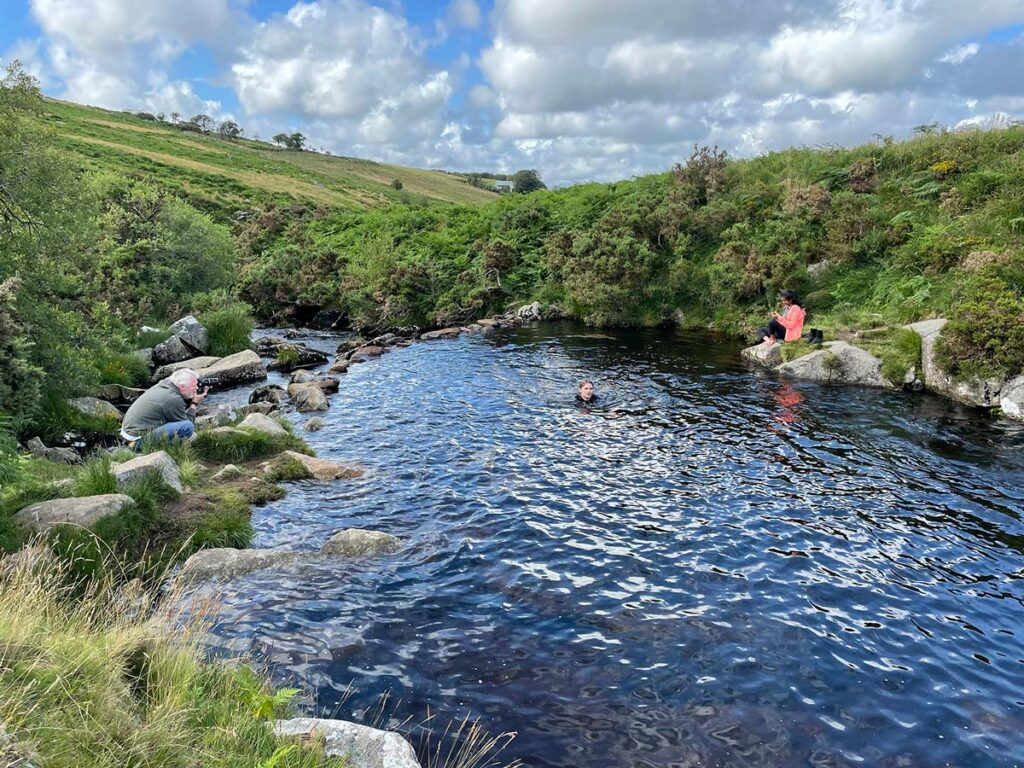 Photographer taking photos of models wild swimming at Cullever Steps, Dartmoor